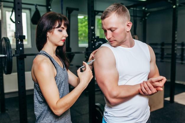 Dziewczyna robi zastrzyk swojemu chłopakowi na siłowni
