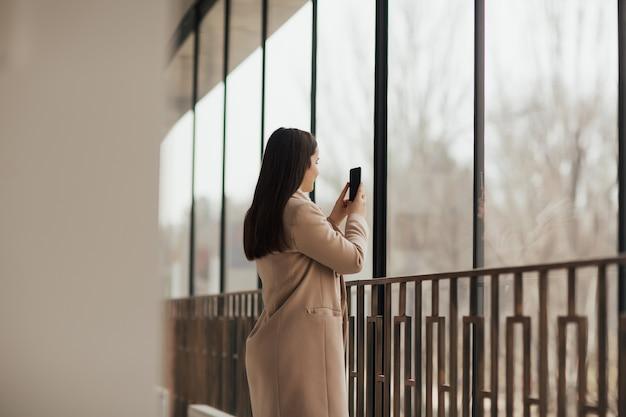 Dziewczyna robi zdjęcia miasta stojąc w pobliżu okna