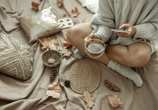 Dziewczyna robi zdjęcie filiżanki herbaty wśród jesiennych liści, jesienna kompozycja.