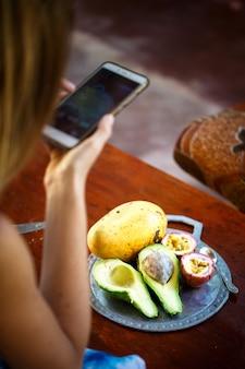 Dziewczyna robi zdjęcie na smartfonie egzotyczne owoce