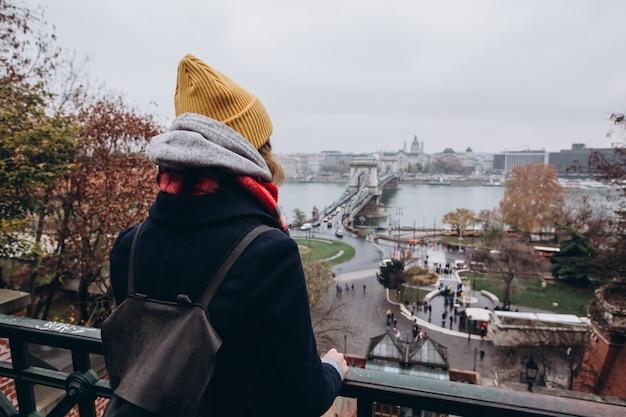 Dziewczyna robi zdjęcie na telefon. dziewczyna w żółtym zimowym kapeluszu zdejmuje. budynek parlamentu w budapeszcie. podróż na węgry. podróż do budapesztu. architektura fotograficzna.