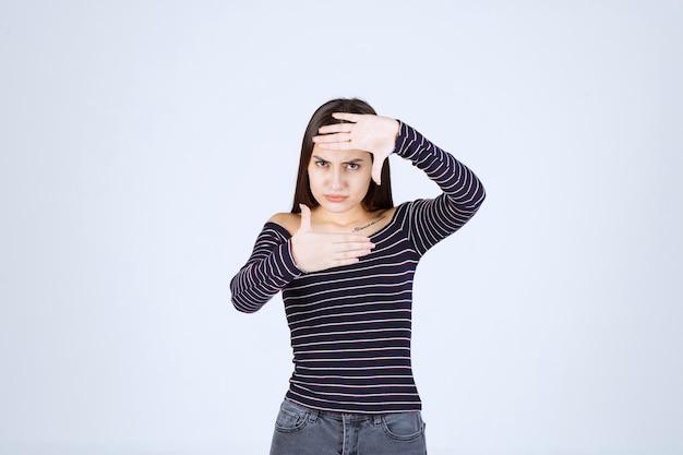Dziewczyna robi zdjęcie przechwytywania dłoni znak.