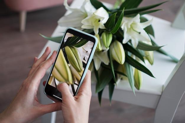 Dziewczyna robi zdjęcie przez telefon. fotografuje bukiet białych lilii. szkolenie z fotografii mobilnej. brak widocznych logo.