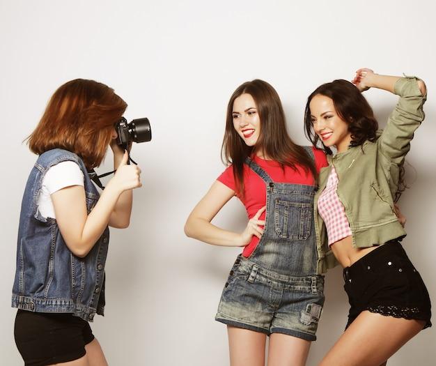 Dziewczyna robi zdjęcie swoim przyjaciołom. pojęcie przyjaźni i zabawy. najlepsi przyjaciele cieszą się chwilą z nowoczesnym aparatem.