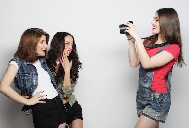 Dziewczyna robi zdjęcie swoim znajomym. koncepcja przyjaźni i zabawy. najlepsi przyjaciele cieszą się chwilą z nowoczesnym aparatem.