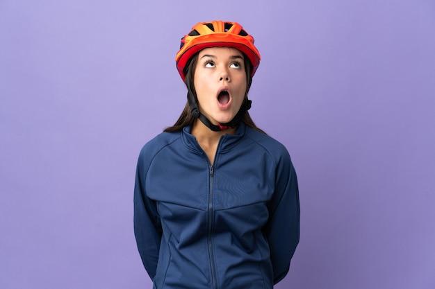 Dziewczyna rowerzysta nastolatek patrząc w górę iz zaskoczonym wyrazem