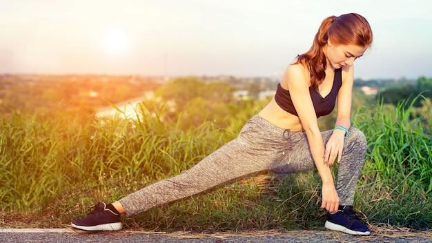 Dziewczyna rozciąga ciało przed porannym bieganiem.