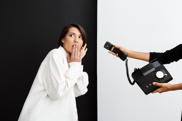Dziewczyna rozciąga się stary telefon podsłucha nad czarny i biały ścianą