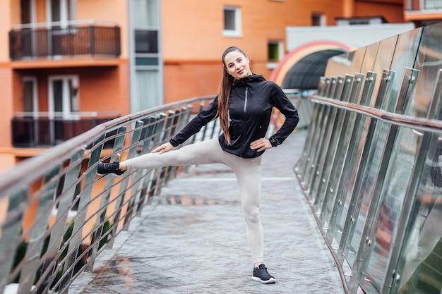 Dziewczyna rozciągająca się latem w mieście, na poranny bieg. tło schodów. top legginsy odzieżowe. zdrowe życie.