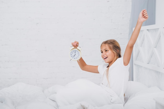 Dziewczyna rozciąganie trzymając zegar
