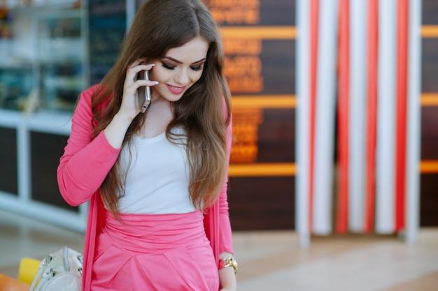 Dziewczyna rozmawia przez telefon i patrząc w podłogę