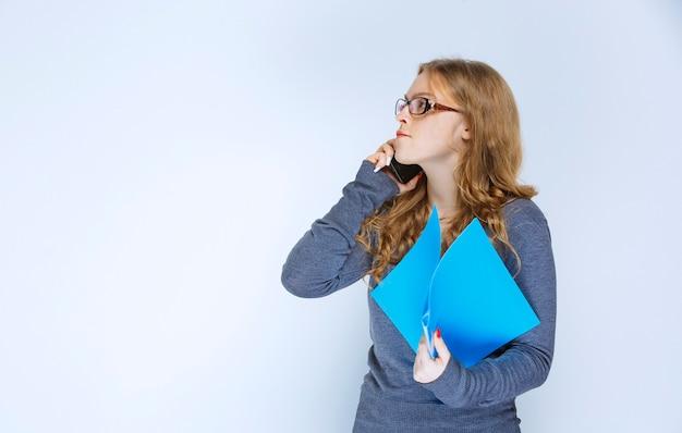 Dziewczyna rozmawia przez telefon i wprowadza poprawki w swoim folderze.