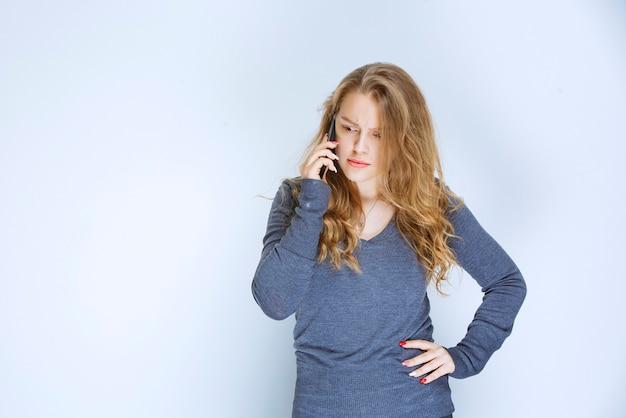 Dziewczyna rozmawia przez telefon i wygląda na przerażoną.