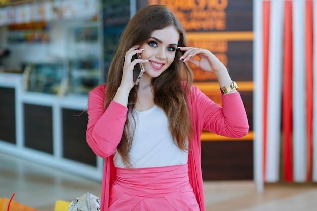 Dziewczyna rozmawia przez telefon podczas uśmiecha się i dotykając jej głowę