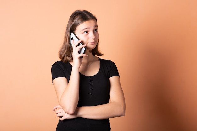 Dziewczyna rozmawia ze zdziwieniem przez telefon na jasnopomarańczowym tle. w dowolnym celu.