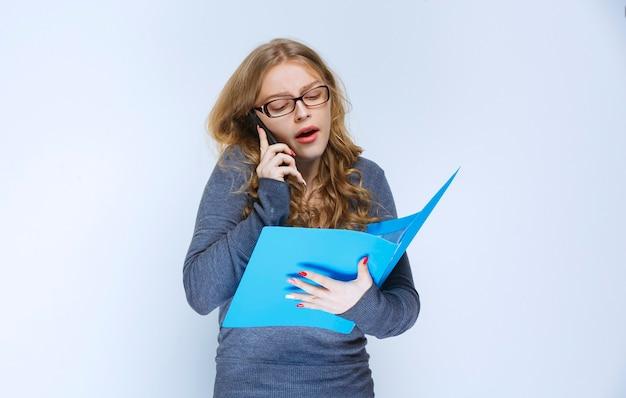 Dziewczyna rozmawiająca z telefonem w sposób niezadowolony i poprawiająca jej niebieską teczkę.