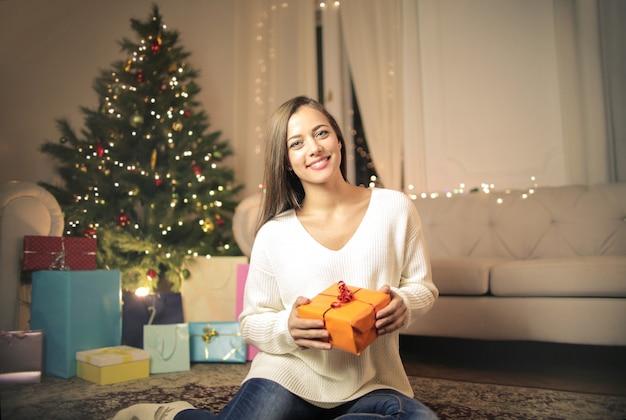 Dziewczyna rozpakowuje prezent na boże narodzenie