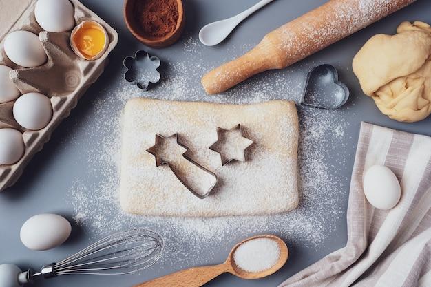 Dziewczyna rozwałkowuje ciasto drewnianym wałkiem do robienia babeczek lub ciasteczek. płaska kompozycja z naczyniami kuchennymi i składnikami, miejsce. koncepcja pieczenia na wakacje.
