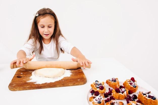 Dziewczyna rozwałkowuje ciasto na ciasta