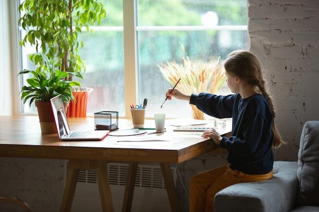 Dziewczyna rysująca farbami i ołówkami w domu, oglądając samouczek online dla nauczycieli na laptopie