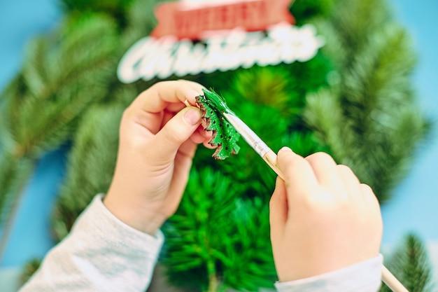 Dziewczyna rysuje choinkę, przygotowując się do nowego roku 2022. wesołych świąt i szczęśliwego nowego roku koncepcja