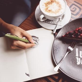 Dziewczyna rysuje filiżankę kawy w notatniku