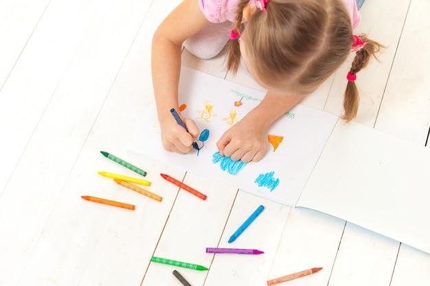 Dziewczyna rysuje kredkami w albumie