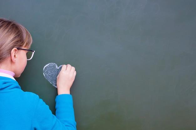 Dziewczyna rysuje serce kredą na tablicy