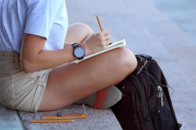 Dziewczyna rysuje w zeszycie siedzącym na chodniku