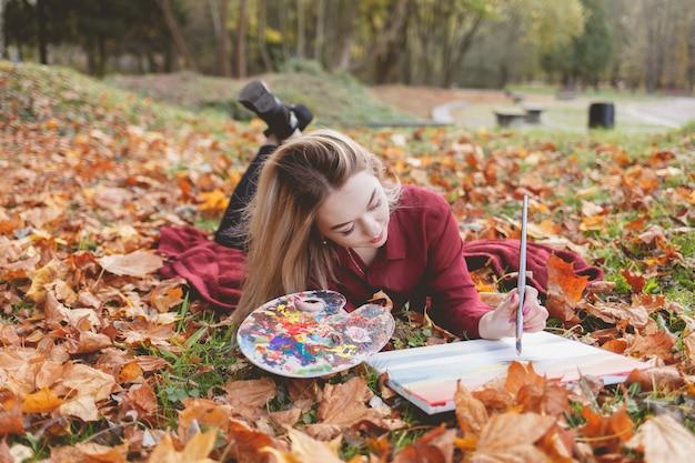 Dziewczyna rysuje zdjęcie w parku