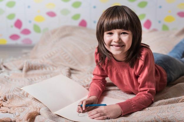 Dziewczyna rysunek na papierze na łóżku