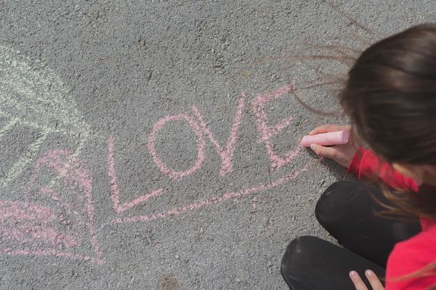 Dziewczyna rysunek z kredą na drodze