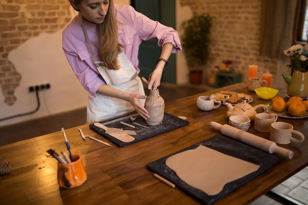 Dziewczyna rzeźbi dzban z gliny w ceramice.