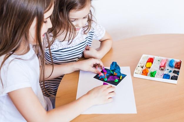 Dziewczyna rzeźbi z plasteliny, gliny, ciasta, majsterkowania w domu, kreatywności podczas wakacji
