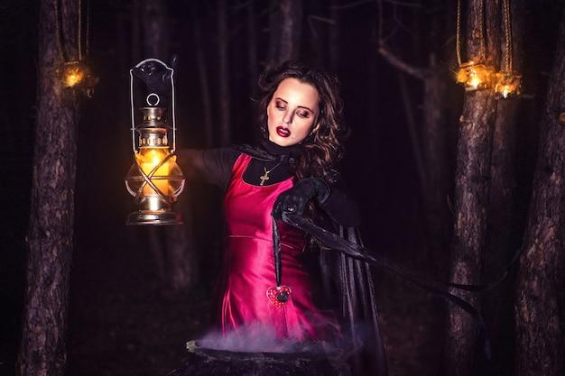 Dziewczyna sama w nocy w lesie warzy miksturę i cuda na ślub, w otoczeniu świec i dymu