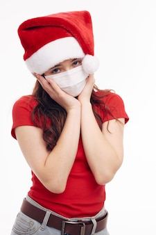 Dziewczyna santa kapelusze czerwona koszulka maska medyczna trzymając się na twarzy