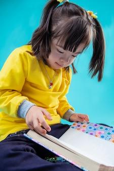 Dziewczyna się kształci. poważne ciemnowłose dziecko z zespołem downa, które swoimi małymi rączkami obserwuje książkę dla dorosłych