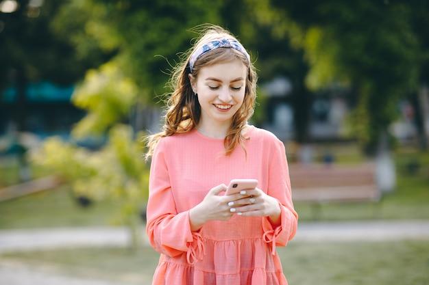 Dziewczyna się śmieje i czyta coś na swoim smartfonie. rozochocona młoda kobieta komunikuje na smartphone podczas gdy chodzący w parku