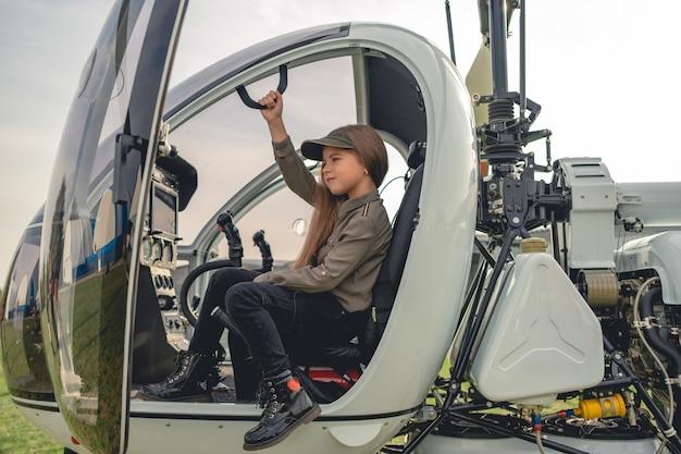 Dziewczyna siedząca na fotelu pilota w nowoczesnym kokpicie helikoptera