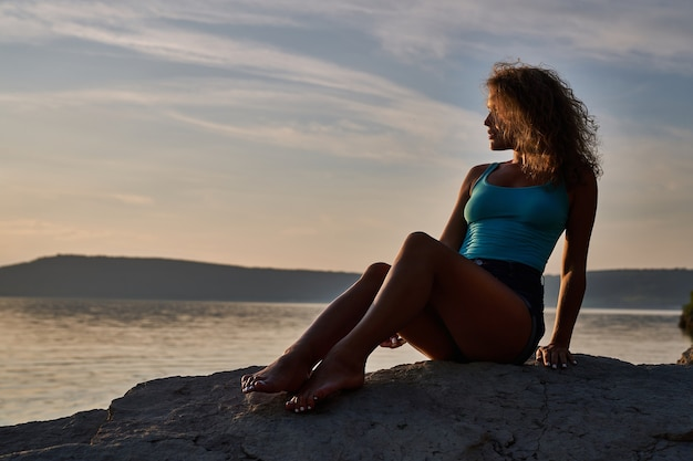 Dziewczyna siedząca na kamieniach i podziwiająca krajobraz