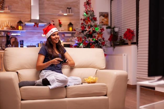 Dziewczyna siedząca na kanapie grająca w gry wideo online za pomocą joysticka do gier