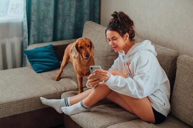 Dziewczyna siedząca na kanapie pokazuje telefon psu