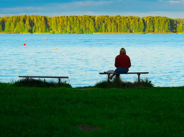 Dziewczyna siedząca na ławce na tle brzegu rzeki
