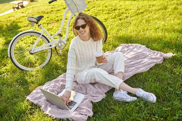 Dziewczyna siedząca na trawie w parku i pracująca na laptopie