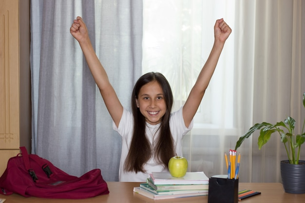 Dziewczyna siedząca przy stole radośnie uniosła ręce do góry plecaka z książkami na stole
