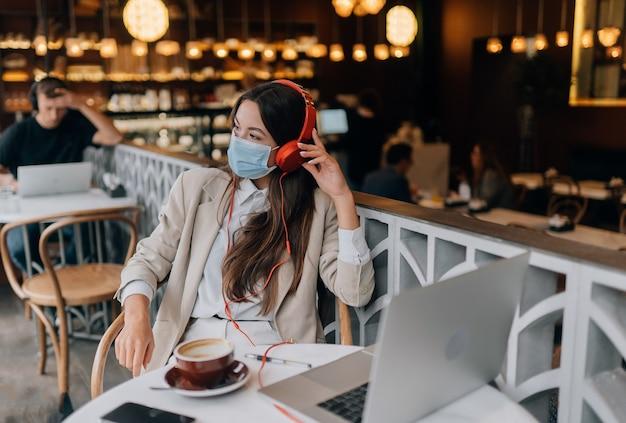 Dziewczyna siedząca w kawiarni ze słuchawkami epidemia koronawirusa