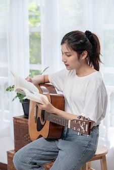 Dziewczyna siedzi i gra na gitarze na krześle.