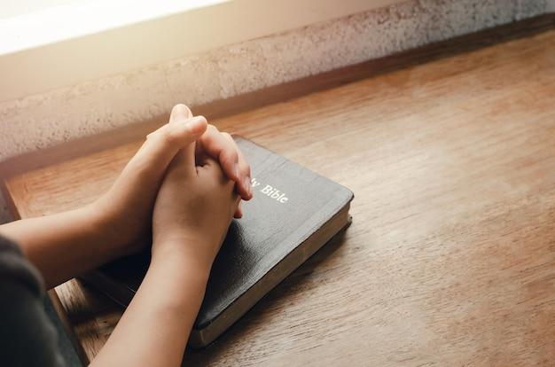 Dziewczyna siedzi i modli się o błogosławieństwa od boga z biblią założonymi rękami w modlitwie biblijnej, duchowej i religijnej, komunikuj się, rozmawiaj z bogiem. miłość i przebaczenie