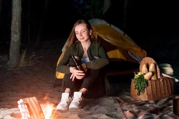 Dziewczyna siedzi i patrząc na ognisko