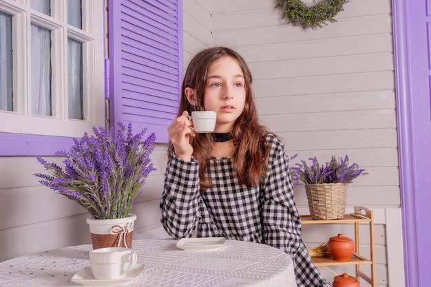 Dziewczyna siedzi i pije. nastoletnia dziewczyna w sukience pije herbatę z białej filiżanki. herbata młoda kobieta kubek